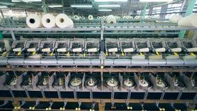 El equipo de la fábrica encanilla los hilos blancos en los ovillos grandes en una instalación metrajes
