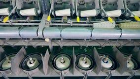 El equipo de la fábrica de la materia textil arrolla la fibra blanca sobre los carretes automáticamente almacen de metraje de vídeo