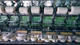 El equipo de la fábrica de la materia textil encanilla los hilos sobre las bobinas almacen de metraje de vídeo