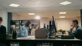 El equipo de los jóvenes está trabajando en sus ordenadores en el cuarto de la oficina metrajes