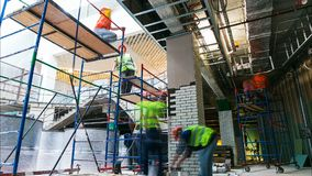 El equipo de los trabajadores hace operaciones de acabamiento en timelapse del andamio almacen de video