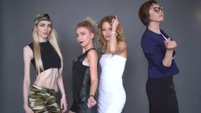 El equipo de muchachas está bailando en la ropa elegante, sonriendo en la cámara aislada sobre fondo negro Mujeres jovenes hermos almacen de video