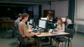 El equipo de 7 personas está trabajando en los ordenadores en su comienza para arriba la oficina almacen de metraje de vídeo