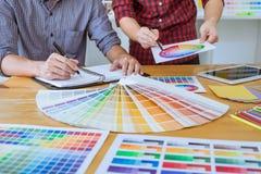 El equipo de reunión creativa del diseñador gráfico que trabaja en nuevo proyecto, elige color de la selección y el dibujo en la  foto de archivo libre de regalías