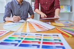 El equipo de reunión creativa del diseñador gráfico que trabaja en nuevo proyecto, elige color de la selección y el dibujo en la  imagen de archivo