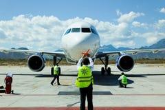 El equipo de tierra dirige un jet a la puerta Imágenes de archivo libres de regalías