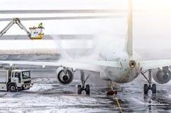 El equipo de tierra proporciona a la de-formación de hielo Están pintando (con vaporizador) el avión, que previene el acontecimie foto de archivo