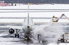 El equipo de tierra proporciona a la de-formación de hielo Están pintando (con vaporizador) el avión, que previene el acontecimie imágenes de archivo libres de regalías