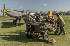 El equipo de tierra se sienta en un jeep WW2 con un mustango P-51 en el backgro Imágenes de archivo libres de regalías