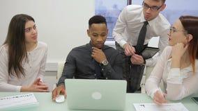 El equipo de trabajo es el hablar, sentándose en el escritorio con el ordenador portátil en compañía almacen de metraje de vídeo