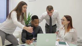 El equipo de trabajo está hablando en el escritorio con el ordenador portátil en oficina moderna metrajes