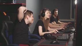El equipo de videojugadores disfruta emocionalmente en la victoria que juega en club del e-deporte almacen de video