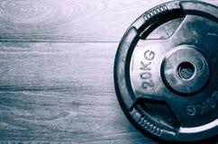 El equipo del ejercicio de la aptitud carga la placa en el piso del gimnasio fotografía de archivo libre de regalías