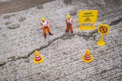 El equipo del mantenimiento para reparar la calle se agrietó, figura miniatura Fotografía de archivo