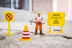 El equipo del mantenimiento para reparar la calle se agrietó, figura miniatura Imagen de archivo libre de regalías