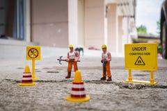 El equipo del mantenimiento para reparar la calle se agrietó, figura miniatura Fotografía de archivo libre de regalías