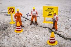 El equipo del mantenimiento para reparar la calle se agrietó, figura miniatura Imágenes de archivo libres de regalías