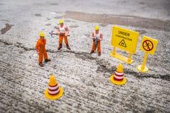 El equipo del mantenimiento para reparar la calle se agrietó, figura miniatura Foto de archivo