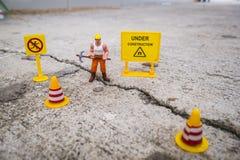 El equipo del mantenimiento para reparar la calle se agrietó, figura miniatura Imagen de archivo