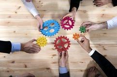 El equipo del negocio conecta pedazos de engranajes Trabajo en equipo, sociedad y concepto de la integración imagen de archivo libre de regalías