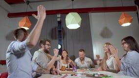 El equipo del negocio de gente joven está doblando las manos juntas y está gritando en oficina metrajes