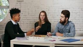 El equipo del negocio de gente joven que goza de la pizza junta en la oficina, millennials agrupa hablar divirtiéndose que compar metrajes
