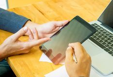 El equipo del negocio está utilizando la tableta para analizar el trabajo Fotografía de archivo