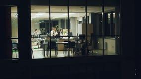 El equipo del negocio del grupo de personas está trabajando en oficina tarde en la noche que habla en el teléfono móvil, discutie almacen de metraje de vídeo