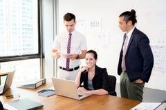 El equipo del negocio que tiene usando el ordenador portátil durante una reunión y presentes Foto de archivo