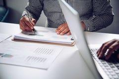 El equipo del negocio que trabaja con los documentos financia y hace tabletas en abierto Foto de archivo