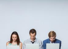 El equipo del negocio que trabaja en los ordenadores portátiles en la oficina fotos de archivo