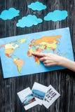 El equipo del turismo de los niños con el mapa y las imágenes en plano oscuro del fondo ponen la maqueta Imágenes de archivo libres de regalías