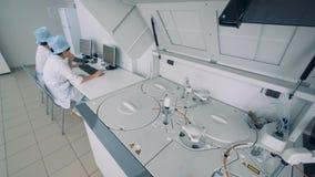 El equipo especial funciona en un cuarto del laboratorio, mientras que las enfermeras se sientan en los ordenadores 4K almacen de metraje de vídeo