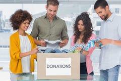 El equipo feliz de voluntarios que sacan viste de una caja de la donación Imágenes de archivo libres de regalías