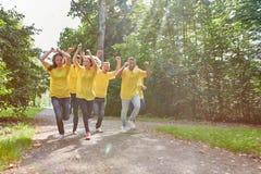 El equipo feliz del ganador está corriendo animar en el parque imagen de archivo
