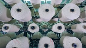 El equipo industrial gira los ovillos con la fibra en una fábrica industrial de la materia textil almacen de metraje de vídeo