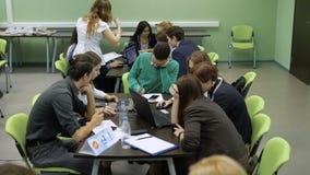 El equipo joven del novato de expertos piensa a través del plan empresarial El trabajo en equipo de servicios a empresas compone  almacen de video