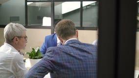 El equipo multiétnico de empresarios trabaja con proyecto en el escritorio en sitio moderno almacen de video