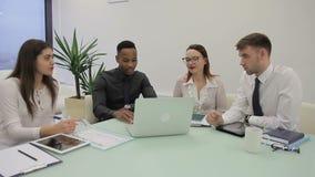 El equipo multiétnico está discutiendo trabajando materias en oficina moderna almacen de metraje de vídeo