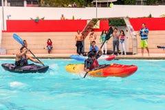 El equipo no identificado compite en la competencia canoeing en una piscina fotografía de archivo libre de regalías