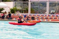 El equipo no identificado compite en la competencia canoeing en una piscina fotos de archivo libres de regalías