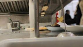 El equipo ocupado de cocineros y los camareros y la cocina proveen de personal la comida preparada y de servicio en una cocina co