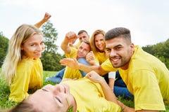 El equipo orgulloso del ganador miente feliz en la hierba foto de archivo
