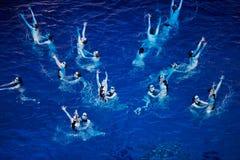 El equipo sincronizado de los nadadores se realiza Foto de archivo