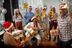 El equipo sonriente del negocio tiene la diversión y baile en el sombrero de Papá Noel en los regalos del partido y del intercamb fotografía de archivo libre de regalías