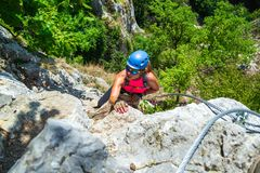 El escalador aventurero, valeroso de la mujer en a vía la ruta del ferrata llamó a Casa Zmeului, una atracción turística popular  fotografía de archivo