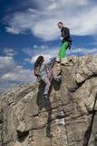 El escalador ayuda a su socio a los ricos la cumbre fotografía de archivo libre de regalías