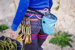 El escalador con su equipo en la correa está listo para hacer su manera para arriba Foto de archivo