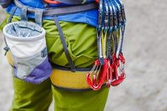 El escalador con su equipo en la correa está listo para hacer su manera para arriba Imágenes de archivo libres de regalías