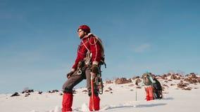 El escalador confiado del hombre se está inclinando en un hacha de hielo, pone su mano a su frente y miradas en la distancia En e metrajes